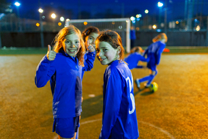 Portrait confident girl playing soccer, gesturing thumbs-upの写真素材 [FYI02188316]