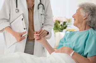 Doctor and aging patient holding hands in hospitalの写真素材 [FYI02188331]