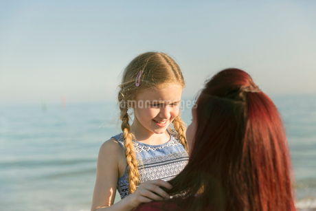 Affectionate mother holding daughter on sunny ocean beachの写真素材 [FYI02188332]