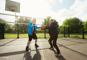 Active senior men friends playing basketball in sunny parkの写真素材 [FYI02188334]