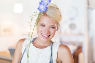 Woman holding flower in rustic kitchenの写真素材 [FYI02188348]