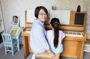 Portrait smiling mother sitting with daughter playing pianoの写真素材 [FYI02188375]