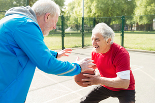 Active senior men friends playing basketball in sunny parkの写真素材 [FYI02188410]