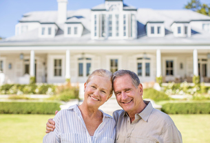 Portrait of smiling senior couple in front of houseの写真素材 [FYI02188435]