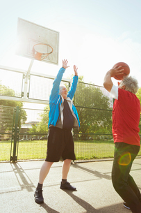 Active senior men playing basketball in sunny parkの写真素材 [FYI02188458]