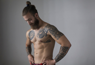 Portrait bare chested man with tattoos and beardの写真素材 [FYI02188459]