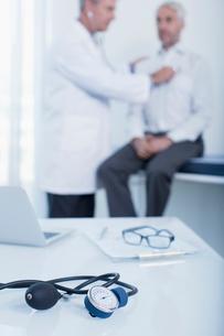 Blood pressure gauge, laptop and patient chart on desk in doctor's office, doctor examining patientの写真素材 [FYI02188478]