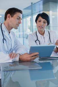 Doctors discussing patient's treatment at desk, using digital tabletの写真素材 [FYI02188509]