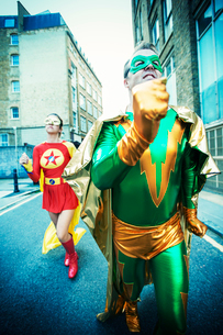 Superhero couple running on city streetの写真素材 [FYI02188518]