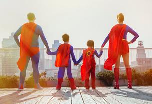 Superhero family standing on city rooftopの写真素材 [FYI02188524]