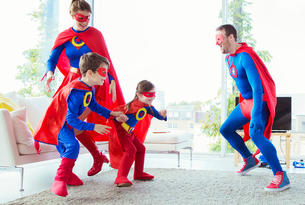 Superhero family chasing each other in living roomの写真素材 [FYI02188525]