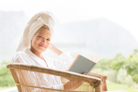 Woman in bathrobe reading outdoorsの写真素材 [FYI02188537]