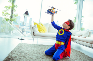 Superhero boy playing with toy helicopter in living roomの写真素材 [FYI02188579]
