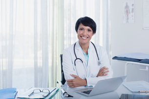 Portrait of smiling female doctor sitting with arms crossed at desk with laptopの写真素材 [FYI02188582]
