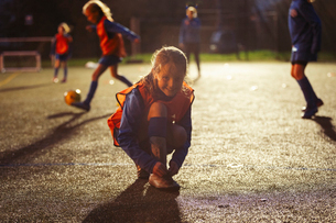 Portrait smiling girl soccer player tying shoe on field at nightの写真素材 [FYI02188589]