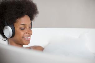 Woman listening to headphones in bathの写真素材 [FYI02188606]