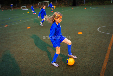 Girl practicing soccer drill on field at nightの写真素材 [FYI02188611]