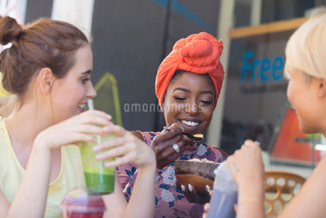 Young women friends drinking smoothies and eating at sidewalk cafeの写真素材 [FYI02188620]