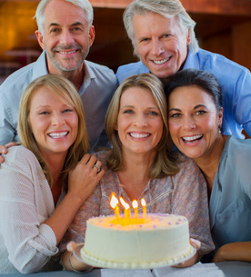 Portrait of smiling mature men and women with birthday cakeの写真素材 [FYI02188640]