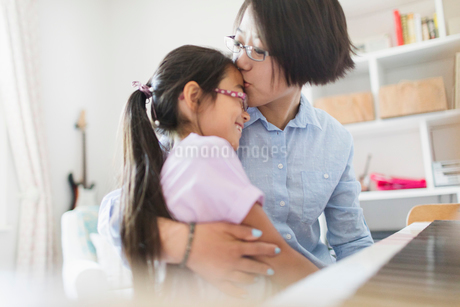 Affectionate mother and daughter hugging, playing pianoの写真素材 [FYI02188687]