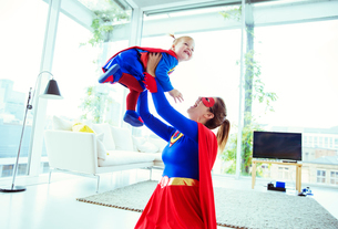 Superhero playing with baby in living roomの写真素材 [FYI02188691]