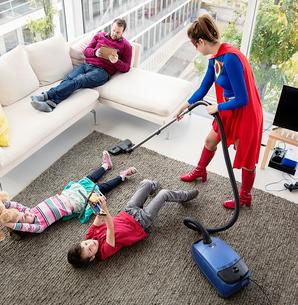 Superhero vacuuming around family in living roomの写真素材 [FYI02188699]
