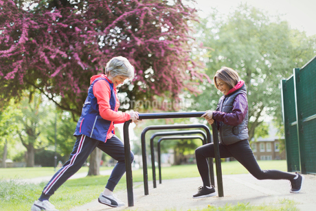 Active senior female runners stretching legs in parkの写真素材 [FYI02188702]