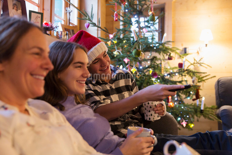 Family relaxing, watching TV in Christmas living roomの写真素材 [FYI02188709]