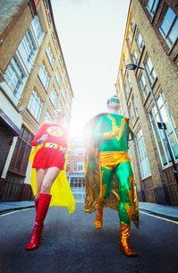 Low angle view of superhero couple running on city streetの写真素材 [FYI02188716]