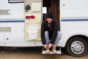 Portrait smiling man tying boot shoelaces in motor home doorwayの写真素材 [FYI02188717]