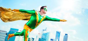 Superhero flying on city rooftopの写真素材 [FYI02188718]