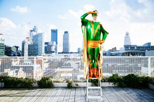 Superhero overlooking view from stepladder on city rooftopの写真素材 [FYI02188752]