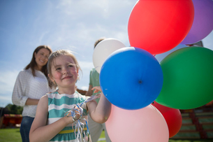 Young girl holding bunch of colorful balloons at sunny dayの写真素材 [FYI02188764]