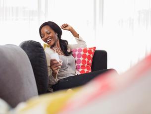 Woman listening to headphones on sofaの写真素材 [FYI02188767]