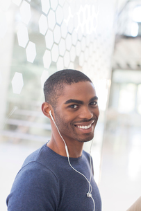 Portrait of smiling young man with earphones in officeの写真素材 [FYI02188778]