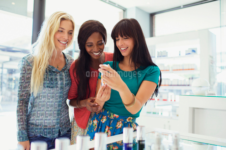 Women examining skincare products in drugstoreの写真素材 [FYI02188790]