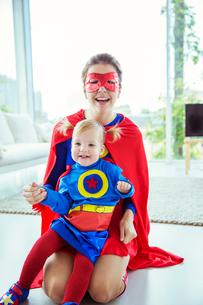 Superhero hugging daughter on living room floorの写真素材 [FYI02188791]
