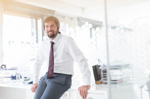 Portrait of smiling businessman wearing shirt and tie leaning on desk in officeの写真素材 [FYI02188793]