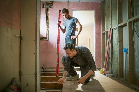 Construction workers using tape measure and level tool in houseの写真素材 [FYI02188803]