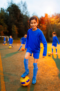 Portrait confident girl practicing soccer on fieldの写真素材 [FYI02188805]
