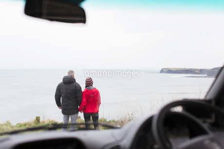 Couple looking at ocean view outside carの写真素材 [FYI02188822]