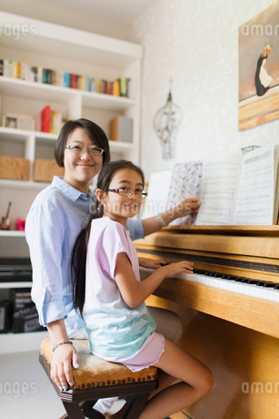 Portrait smiling mother and daughter playing pianoの写真素材 [FYI02188853]