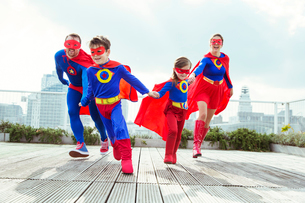 Superhero family playing on city rooftopの写真素材 [FYI02188863]