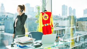 Businesswoman talking on cell phone with superhero costume behind herの写真素材 [FYI02188866]