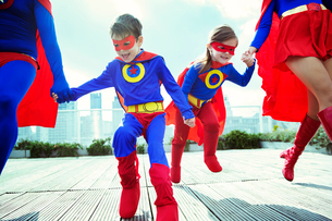 Family of superheroes running on city rooftopの写真素材 [FYI02188942]