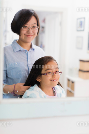 Mother fixing daughters hair in bathroom mirrorの写真素材 [FYI02188966]