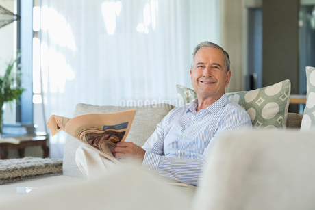 Older man reading newspaper on sofaの写真素材 [FYI02188969]