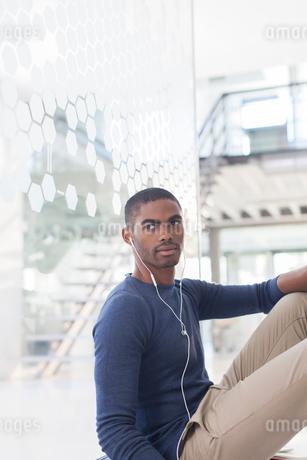 Man listening to music on earphones, sitting on floor in office corridorの写真素材 [FYI02188973]