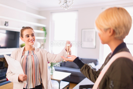 Real estate agent giving keys to woman in apartmentの写真素材 [FYI02188980]