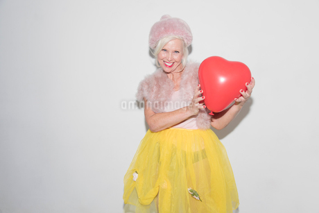 Portrait smiling, confident senior woman holding heart-shape balloonの写真素材 [FYI02188988]